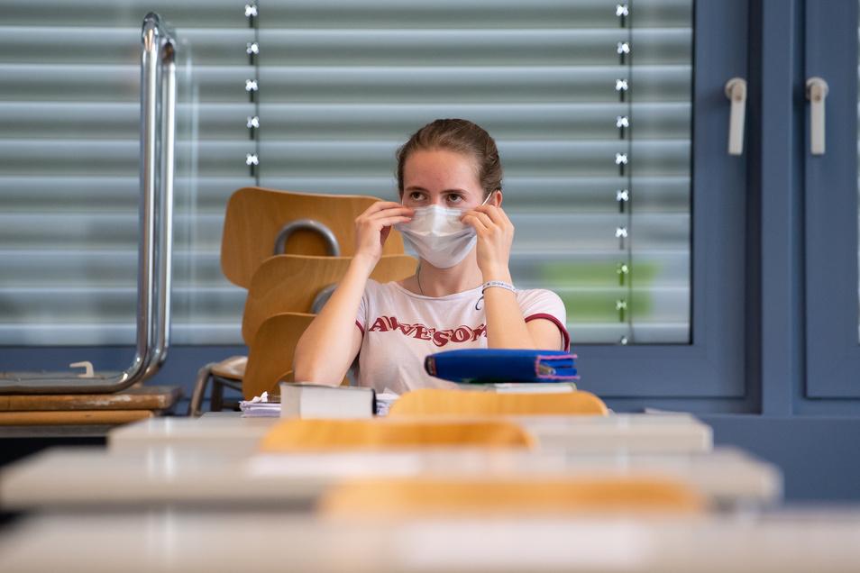 Eine Schülerin rückt im Klassenzimmer ihren Mund-Nasen-Schutz zurecht. Auch in der Döbelner Region werden ab dieser Woche wieder mehr Kinder und Jugendliche die Schulen besuchen.