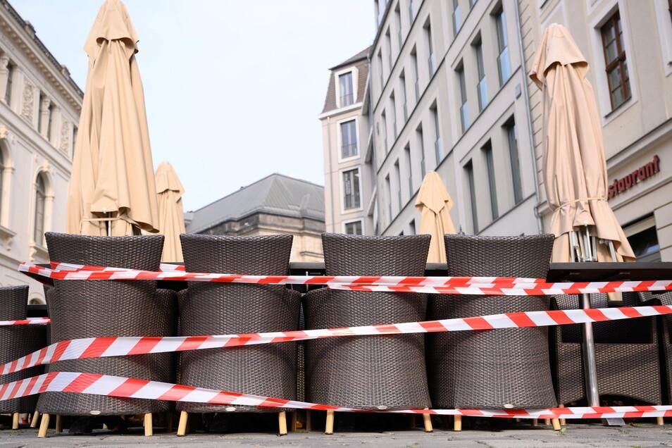 Ein Absperrband umgibt Tische und Stühle vor einem Restaurant auf dem Dresdner Neumarkt.