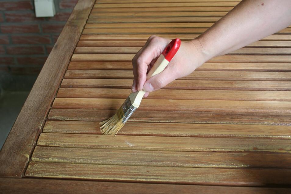 Holz-Öl wird mit einem Pinsel dünn und gleichmäßig aufgetragen.