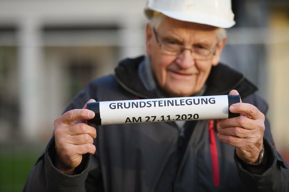 Bürgermeister Bruno Scholze zeigt die sogenannte Zeitkapsel, ein Behältnis mit einer aktuellen Sächsischen Zeitung, Münzen und Kinderzeichnungen, die bei der Grundsteinlegung mit in der Bodenplatte versenkt wurde.