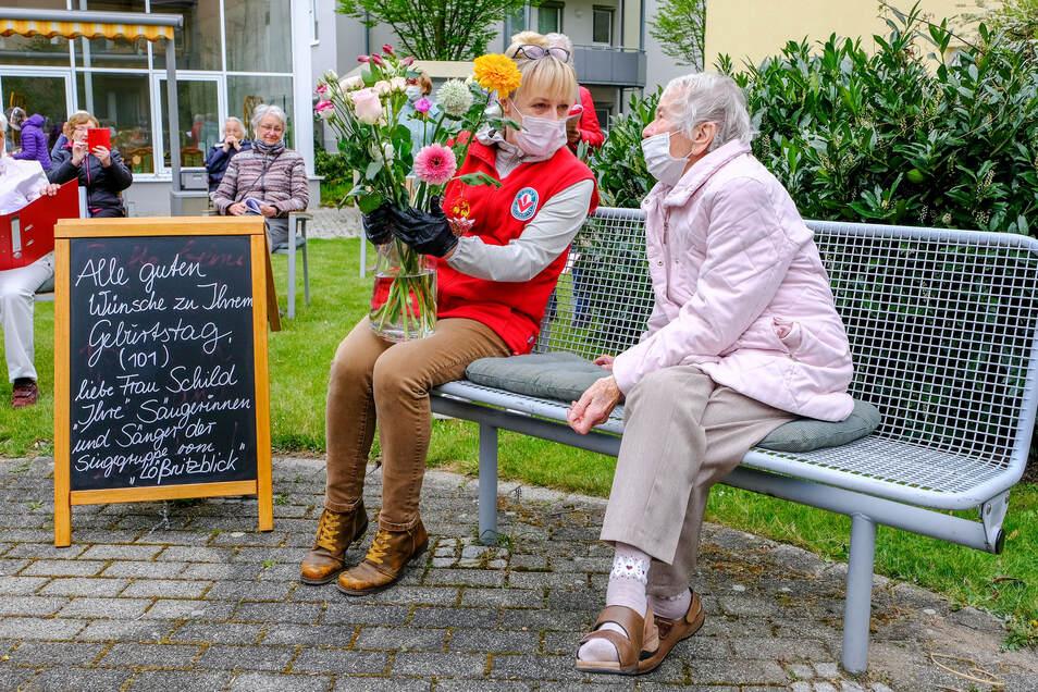 """Mehr Nähe: Nach dem dritten Lied nimmt die Jubilarin Margareta Schild bei ihren Sangesfreunden im Innenhof Platz. Wohnparkleiterin Katrin Hanitsch überreicht der 101-Jährigen einen großen Blumenstrauß. """"So ein Jubiläum haben wir noch nie gehabt"""", sagt sie"""