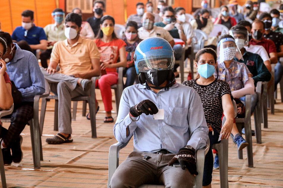 Zahlreiche Menschen ab 18 Jahren warten im Impfzentrum auf dem Radha Soami Satsang-Gelände in Neu Delhi darauf, die erste Dosis des Corona-Impfstoffs von Astrazeneca zu erhalten.