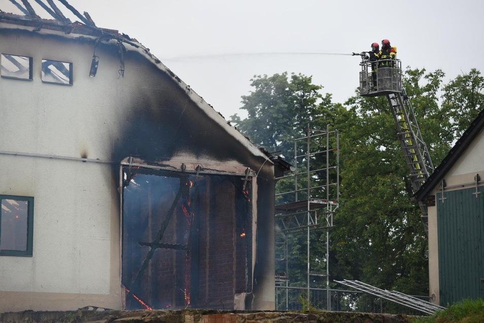 Über eine Drehleiter versuchen Feuerwehrleute die Scheune von oben zu löschen.