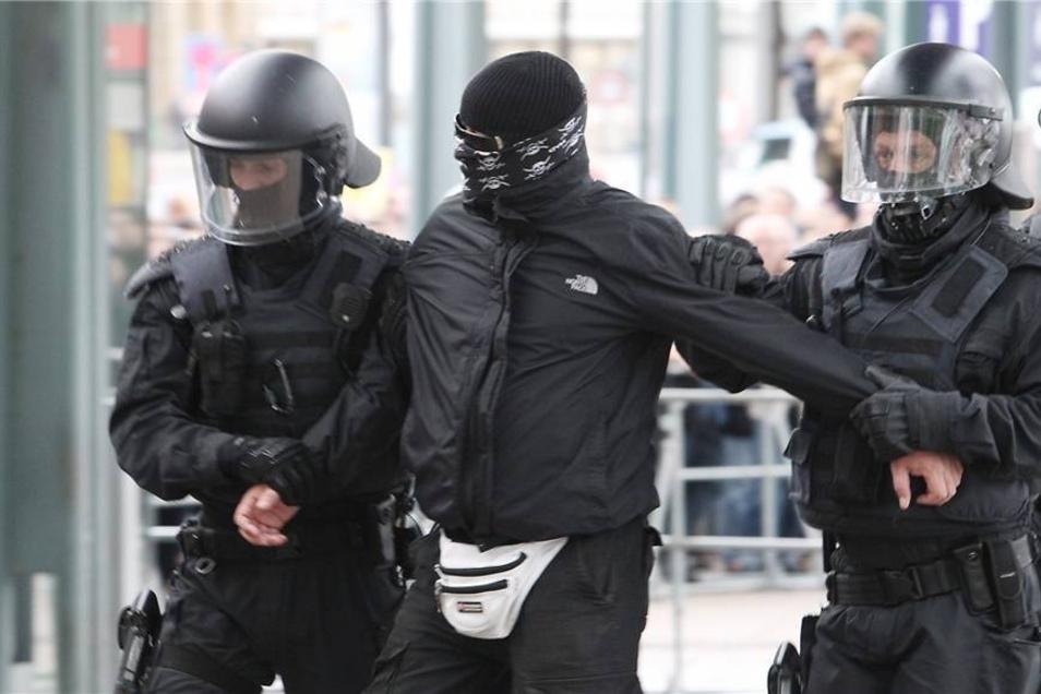 Polizisten nehmen  einen vermummten Mann in Gewahrsam.