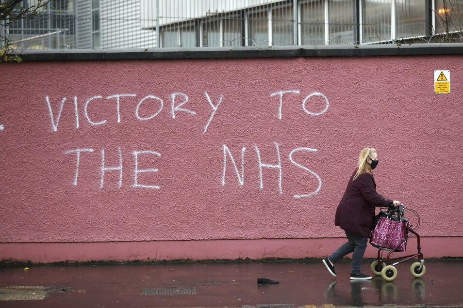 """Eine Frau in Belfast geht an einer Wand vorbei, an der """"Victory to the NHS"""" (""""Sieg der NHS"""") gesprüht steht. Auf den National Health Service sind die Engländer stolz wie auf einen runtergerockten Fußballklub."""