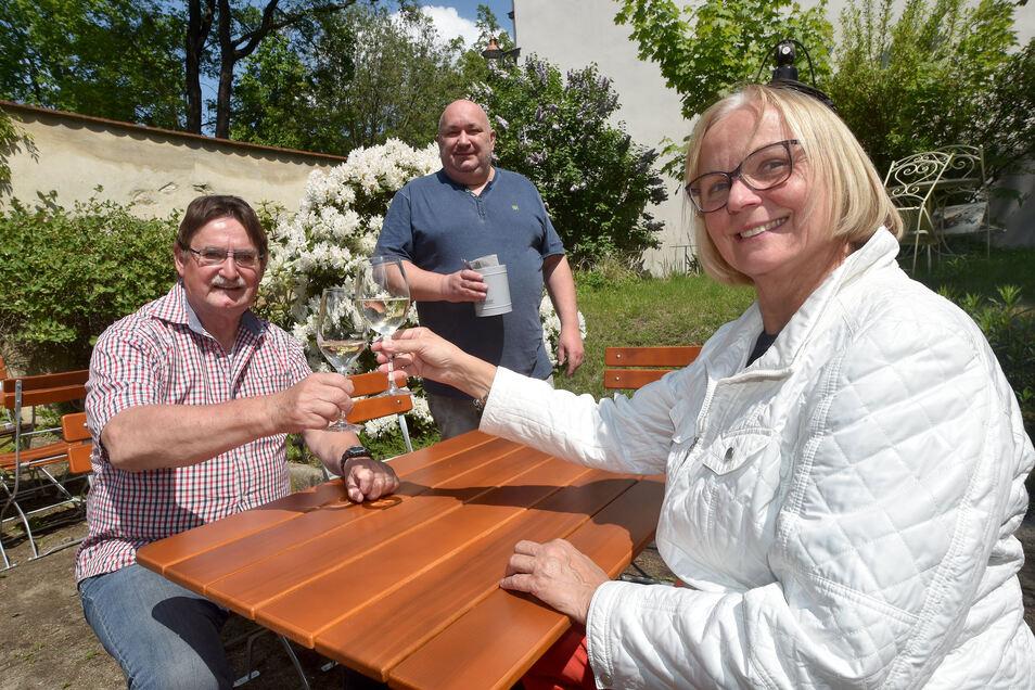 Sigrid und Manfred Gey stoßen im Biergarten vor Gastwirt André Matthausch (Hintergrund) auf die Wiedereröffnung der Seeger Schänke in Zittau an.