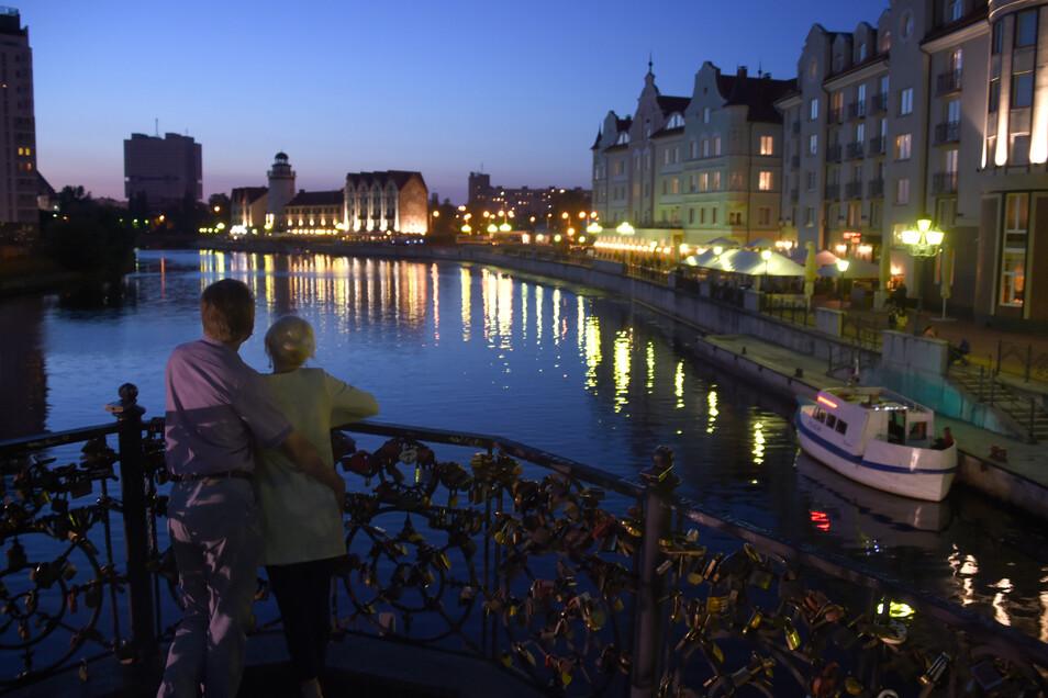 Ein Paar in Kaliningrad genießt den Blick auf einen Kanal und die Uferpromenade.
