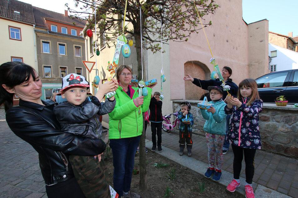 Ilona John (in Grün) hat einen der Bäume in ihrer Pflegerabatte in Roßwein mit Osterüberraschungen behängt. Diese haben schnell ihre Abnehmer gefunden.