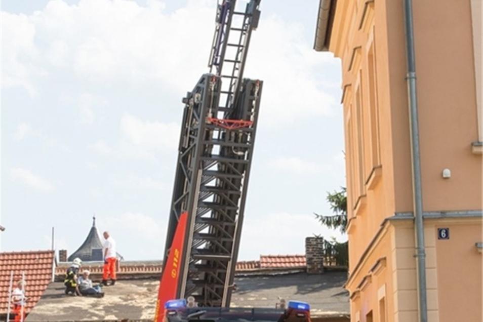 An der Muntschickstraße in Bischofswerda halfen Feuerwehrleute mit der Drehleiter bei einem Rettungseinsatz. Ein Mann hatte an einem Hochsommertag ein Dach repariert. Die Folge war ein Schwächeanfall. Die Leiter wurde hier nur zum Teil ausgefahren. Bis zu
