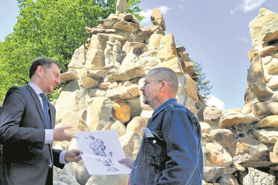 Ministerpräsident Michael Kretschmer ließ sich von Steinbildhauer Dirk Bretschneider den Aufbau der Grotte erklären, die anhand einer Animation erfolgte. Zum Wiederaufbau wurden alte Steine katalogisiert, gesäubert, mit neu angefertigten Steinen verbaut.