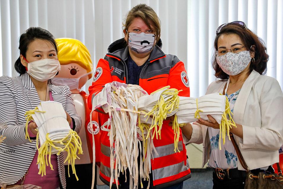 Pham Thi Thu Hien Leipert (r.) und Nguyen Tuyet Nhung (l.) vom Vietnamesischen Verein Harmonie übergeben beim Roten Kreuz Löbau 500 Masken an Geschäftsführerin Silke Seeliger.
