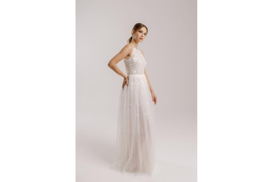 Dieses Kleid ist leicht und zart. Der hauchdünne Stoff umspielt das Bein der Braut.