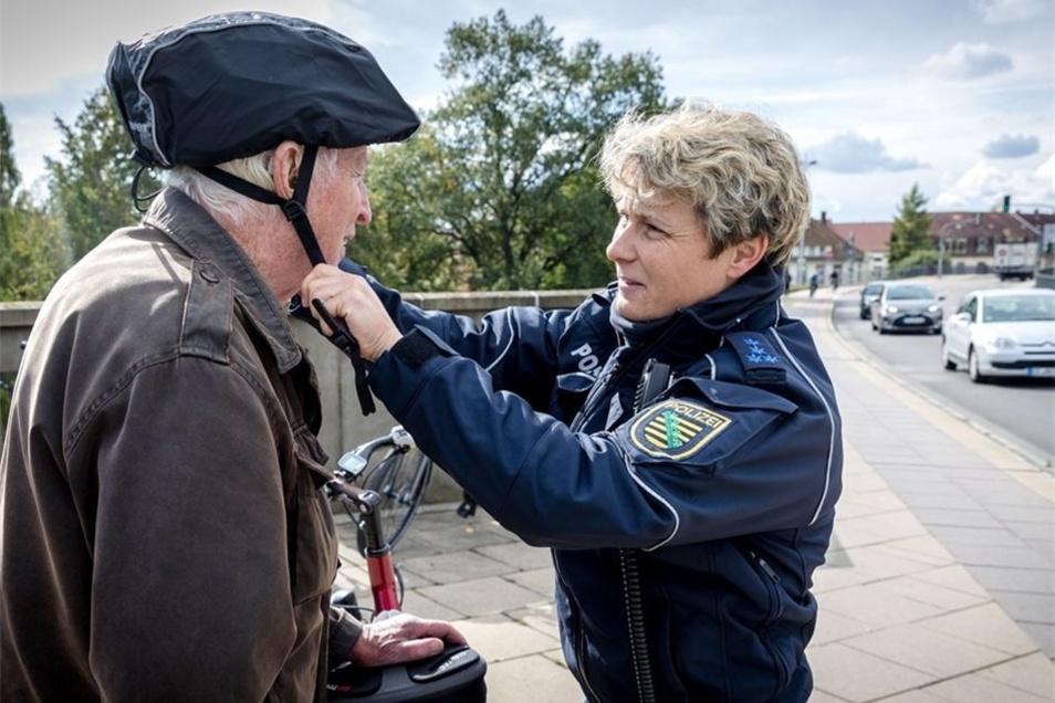Hauptmeisterin Lange richtet den Fahrradhelm von Rentner Albert Jäger.