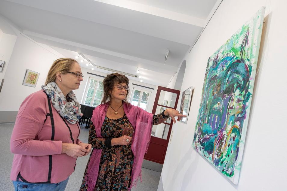 """Anke Israel (links), Mitarbeiterin der Kuppelhalle, und Künstlerin Michele Cyranka (re.) in der Ausstellung """"Bei den Faunen zu Gast"""" in der Kuppelhalle Tharandt."""