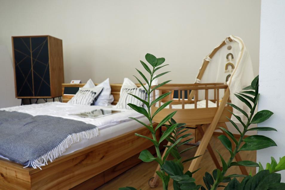 """Chris-Albert Gebhardt, 3. Lehrjahr bei den Deutschen Werkstätten Hellerau, """"Hygge Massivholzbett"""": Das Gesellenstück verfügt über vier Bettkästen und wirkt dennoch wohnlich, leicht und gemütlich. Die Bettkästen können über einen Taster bequem geöffnet werden. Die integrierten Bettlampen sind mit warmen LED ausgestattet und können einfach ein- und ausgeklappt werden. Im gleichen """"Hygge""""-Stil hat der Vogtländer im Kreativkurs dazu passend eine Vollholz-Wiege und einen Schrank gebaut."""