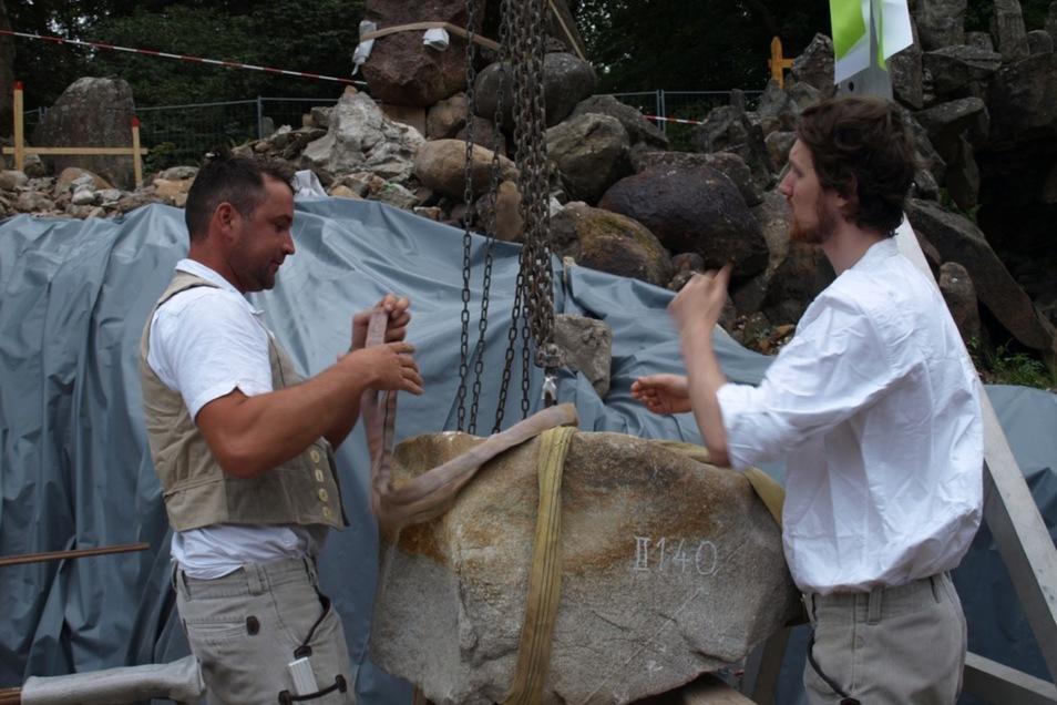 Die Mitarbeiter der Steinmetzfirma Schubert setzten den Originalgrundstein mit technischer Hilfe und viel Fingerspitzengefühl auf das Fundament der Grotte.