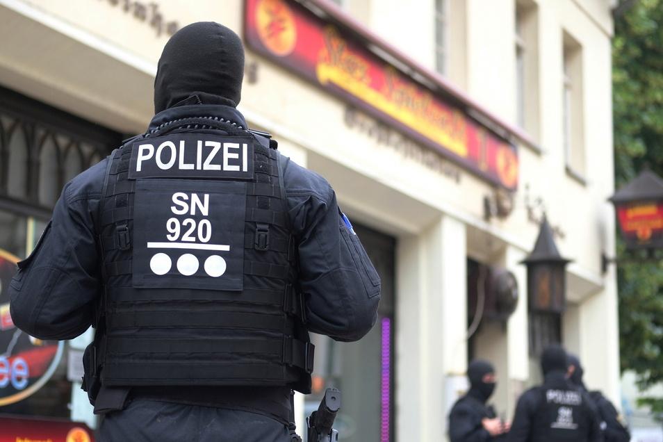 Polizisten stehen vor einem Cafe in der Leipziger Eisenbahnstraße. Dort fand am Donnerstag eine Razzia des Hauptzollamtes statt.