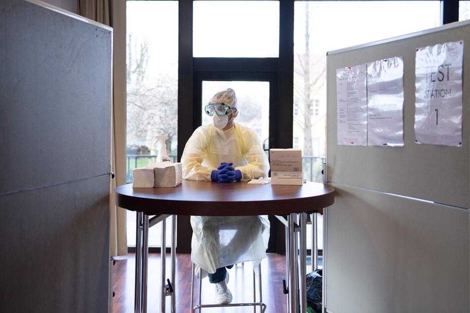 Symbolbild: Ein Mitarbeiter sitzt in einem Corona-Schnelltest-Zentrum.