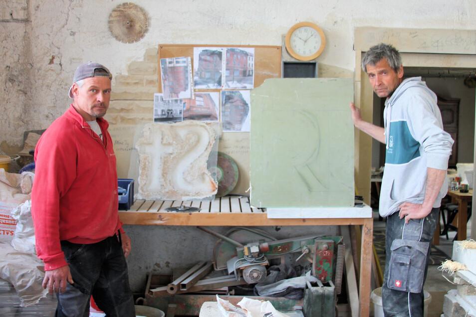 """Udo Tunack (r.) und links sein Mitarbeiter Sven Scholz. Derzeit wird der neue Schriftzug für das Haus Kaffee Starke am Riesaer Rathausplatz vorbereitet. Im Bild die Skizze für den fehlenden Buchstaben """"R"""", der bei der Rösterei fehlte. Rechts neben Scholz"""