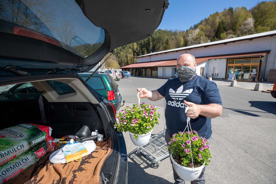 Ronald Lerch aus Bad Schandau lädt am RHG-Markt in Rathmannsdorf zwei Blumenampeln für seine Frau ein.