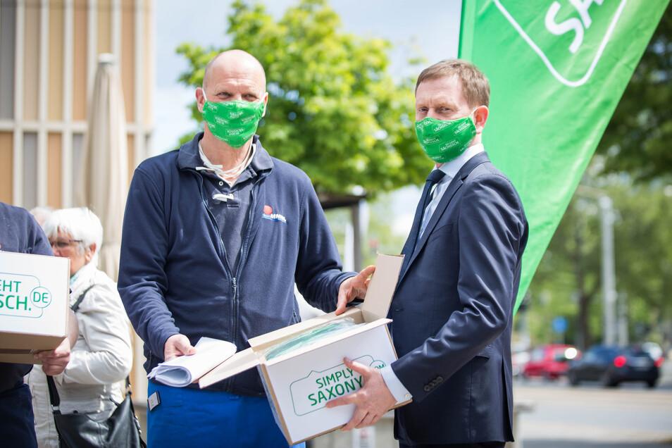 """Als Dankeschön gab es von Ministerpräsident Michael Kretschmer (CDU, r.) Mund-Nase-Masken für die Mitarbeiter von Peter Simmel. Der Besuch war Teil der Werbeaktion """"So geht sächsisch""""."""