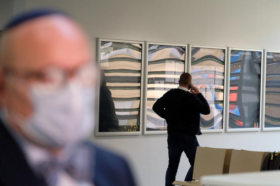 """Der Angeklagte Kevin A. (r.) im Foyer des Amtsgerichtes, während im Vordergrund """"Shalom""""-Chef Uwe Dziuballa mit Pressevertretern spricht."""