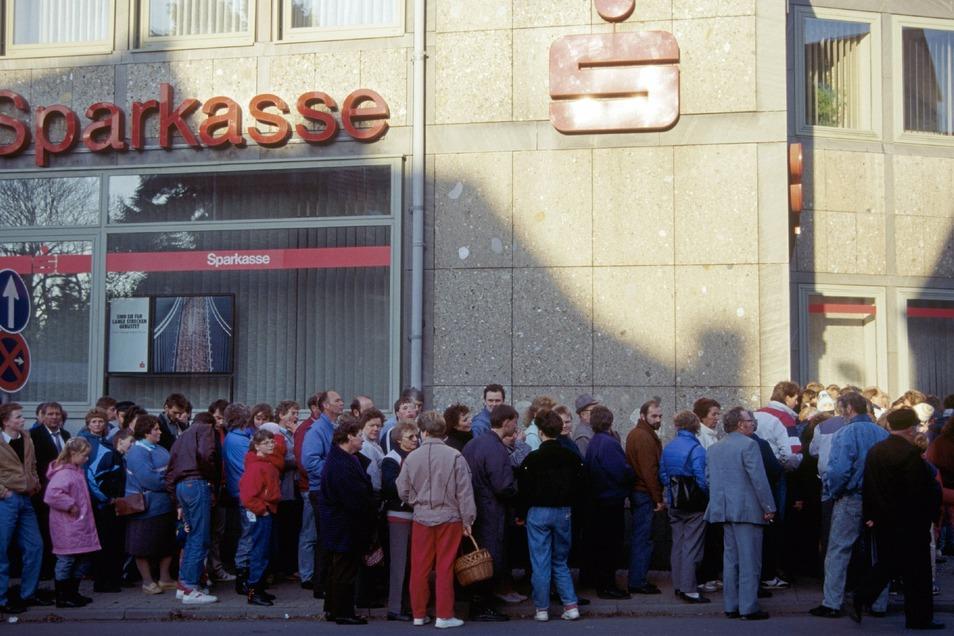 DDR-Bürger stehen im November 1989 vor der Kreissparkasse in Duderstadt.(Niedersachsen). Dort bekam jeder 100 Westmark als Begrüßungsgeld.