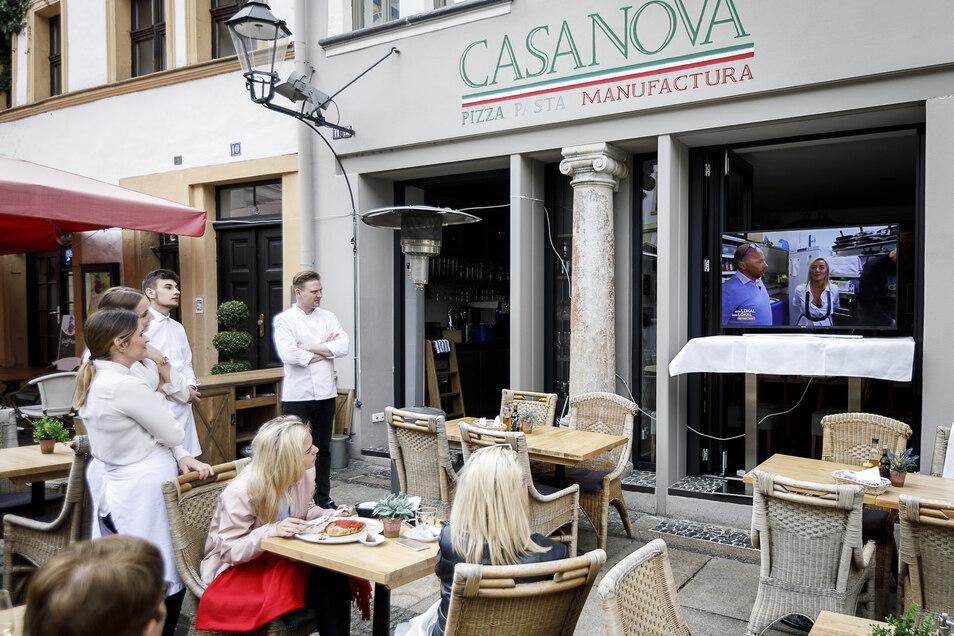"""Angestellte und Gäste des """"Casa Nova"""" am Untermarkt schauen die Fernsehsendung """"Mein Lokal, Dein Lokal"""". Das war am Montag. Gestern wurde der Bildschirm wegen des kalten Wetters drin aufgebaut."""