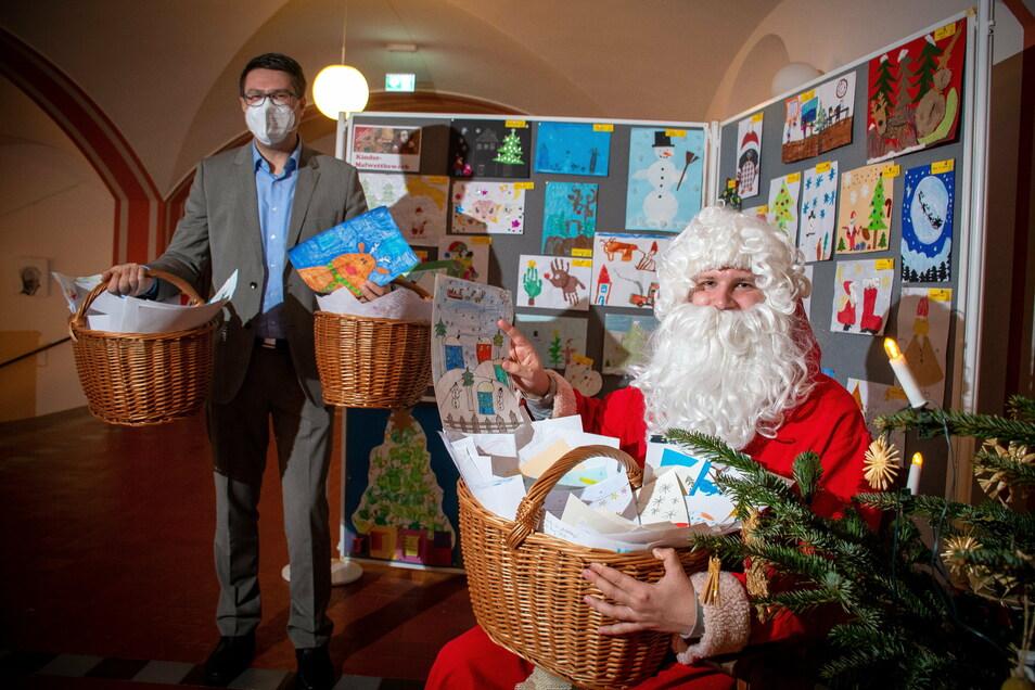 Der Weihnachtsmann und Döbelns Oberbürgermeister Sven Liebhauser präsentieren die Zeichnungen, die viele Kinder zum Weihnachtsmann-Malwettbewerb eingesandt haben.