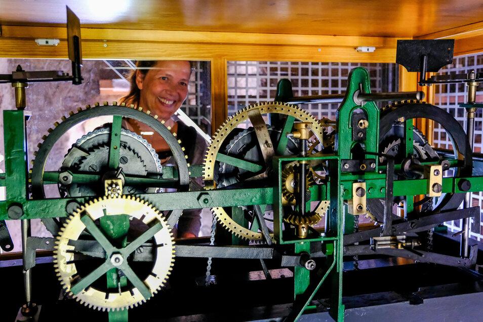 Messingräder, die ineinandergreifen. Pfarrerin Annegret Fischer freut sich über das wiederhergestellte Uhrwerk der Friedenskirche