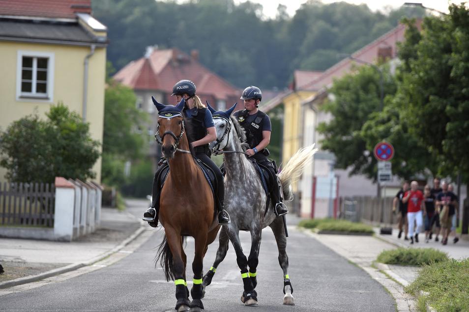 Berittene Polizisten sind auf der Bahnhofstraße in Ostritz unterwegs.