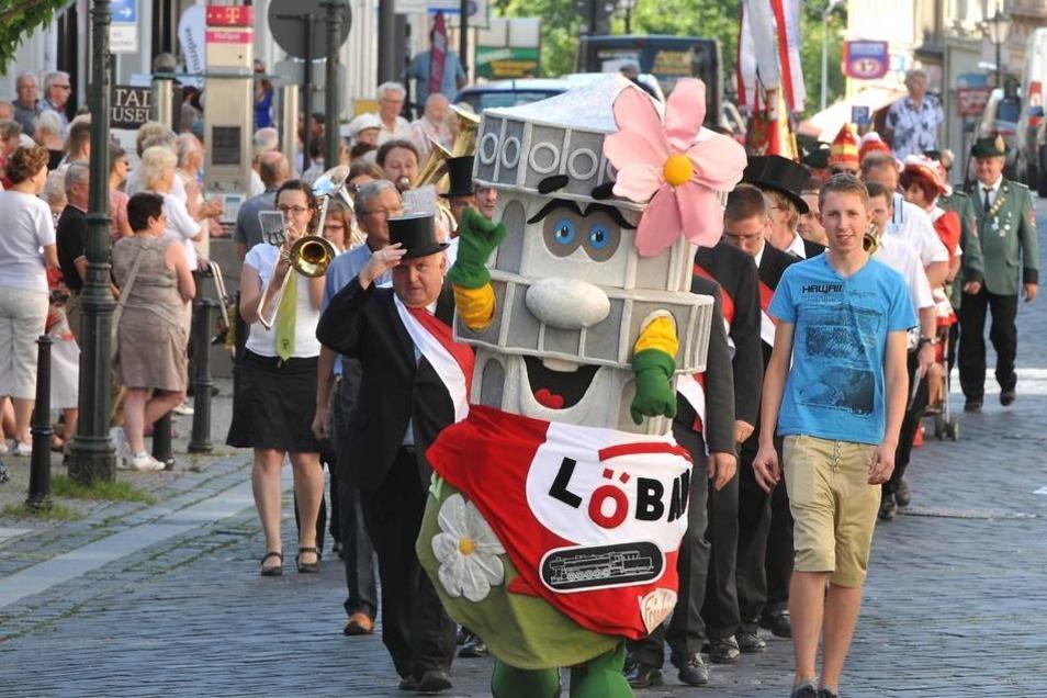 Der Festumzug ist vom Altmarkt bis zum Wettiner Platz gegangen, mit musikalischer Begleitung und unter den Blicken vieler Zuschauer. Vorneweg laufen Löbaus Oberbürgermeister Dietmar Buchholz (parteilos) und das Maskottchen, Turmmännchen Friedrich.