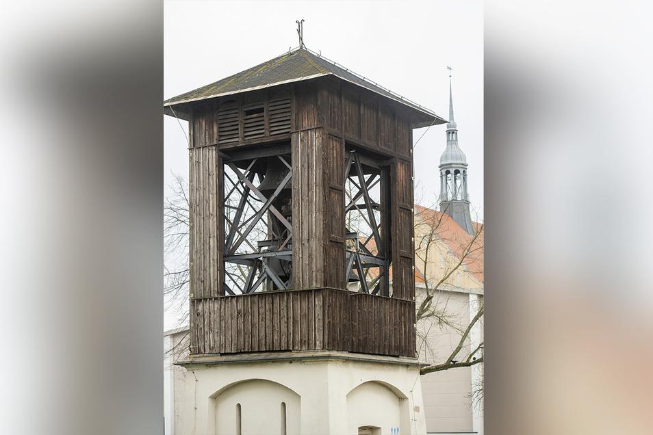 Zwei Türme, deren Geschichte miteinander verbunden ist: der auf dem Heidenauer Gymnasium (Hintergrund) und der frei stehende Glockenturm.