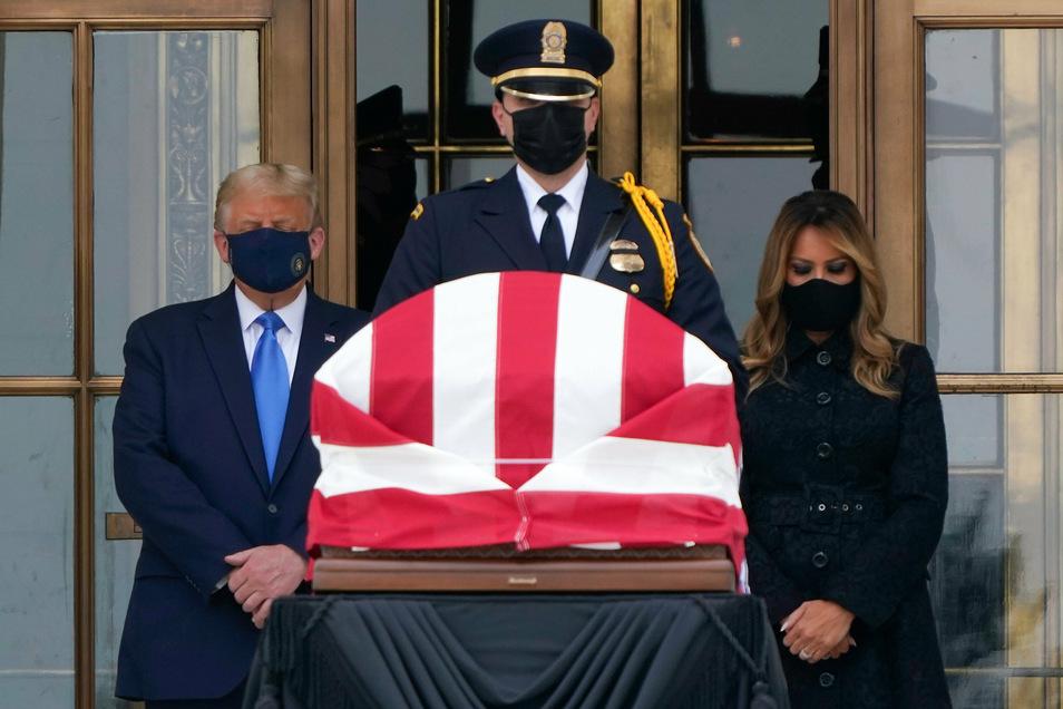 Donald und Melania Trump stehen vor dem Supreme Court neben einem mit der US-Flagge umhüllten Sarg, in dem die am 18.09.2020 gestorbene Juristin Ginsburg aufgebahrt ist.
