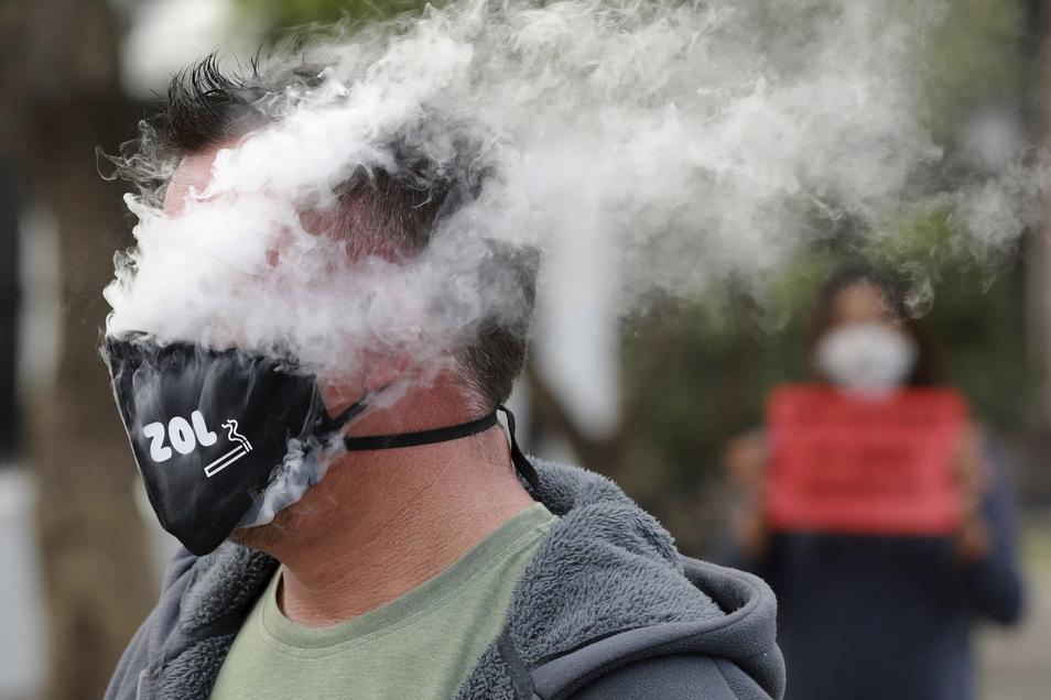 Rauchzeichen mit Maske: Ein Demonstrant atmet während eines Protests vor dem Parlament gegen das Tabakverbot Rauch aus.