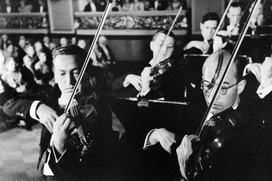 """Die Dresdner Philharmonie spielt im NS-Propagandafilm """"Symphonie eines Lebens"""" (1942) in der alten Berliner Philharmonie mit: Erster Konzertmeister Bernhard Hamann (l.) und Konzertmeister Arthur von Freymann."""