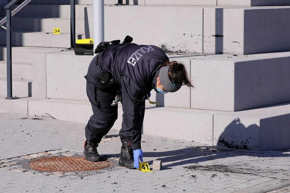 Beamte des Landeskriminalamtes sichern vor dem Hotel die Spuren, darunter auch einen Pflasterstein, mit dem offenbar eine Scheibe des Hotels eingeschlagen wurde.