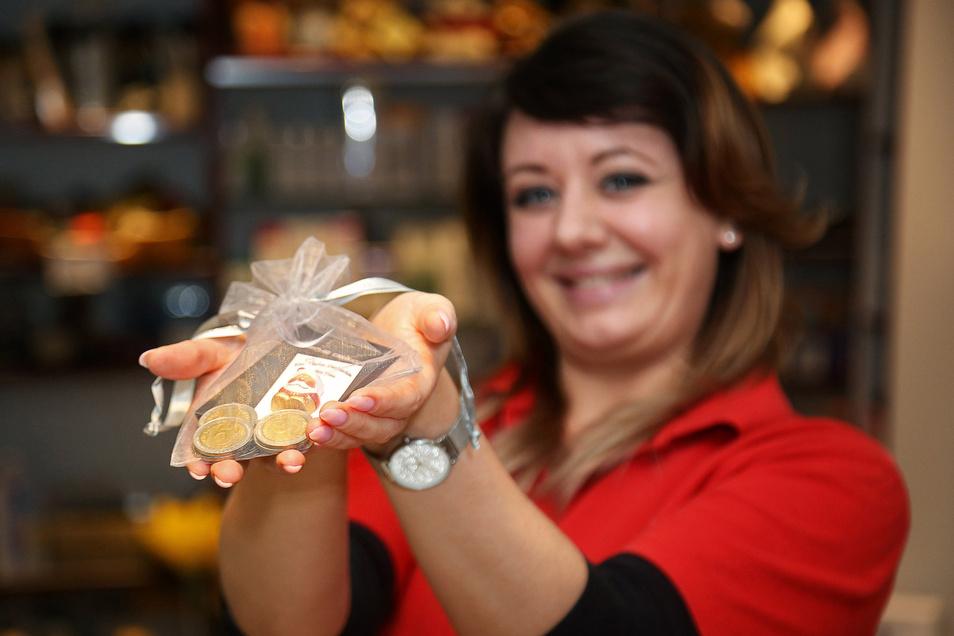 Jana Heimbold zeigt die Geschenk-Dukaten, die die Parfümerie Vitalis in Riesa als Alternative zu normalen Gutscheinen anbietet. Zum Weihnachtsgeschäft waren die Münzen der Renner schlechthin, sagt Chefin Sabina Richter.