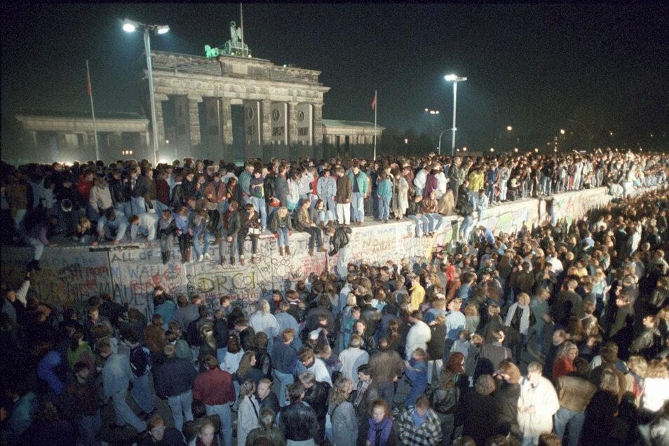Menschen auf der Berliner Mauer vor dem Brandenburger Tor in der Nacht vom 9. auf den 10. November 1989.
