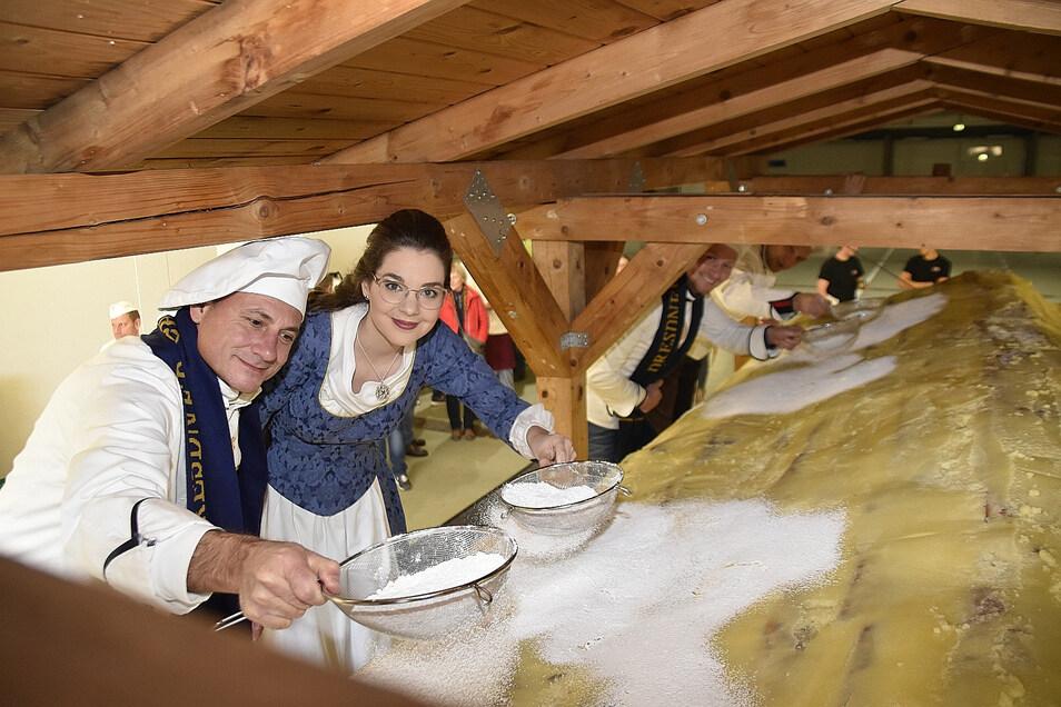 Stollenmädchen Veronika Weber hilft Bäcker Tino Gierig beim Zuckern des Riesenstriezels.
