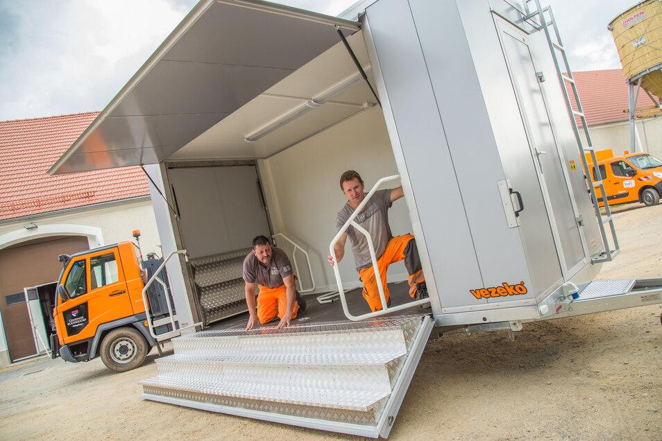 Uwe Bork und Mike Wagenknecht von der kommunalen Kodersdorfer Gesellschaft KoIS kümmern sich um den Innenausbau des neuen Eventwagens der Gemeinde.