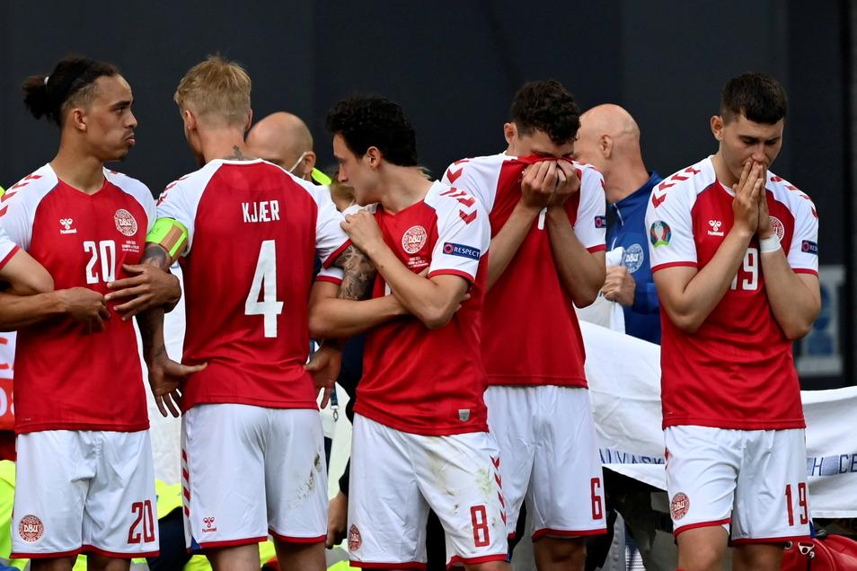 Dänische Spieler bilden einen Sichtschtz um ihren Mannschaftskameraden Christian Eriksen, der von Sanitätern während des Spiels versorgt wird.