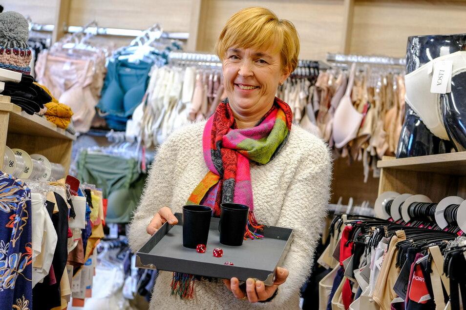 Susan Gommlich hält die Becher mit den drei Würfeln auf dem Spielbrett. Nach jedem Einkauf können Kunden um einen Nachlass von drei bis 18 Prozent beim nächsten Ladenbesuch spielen.