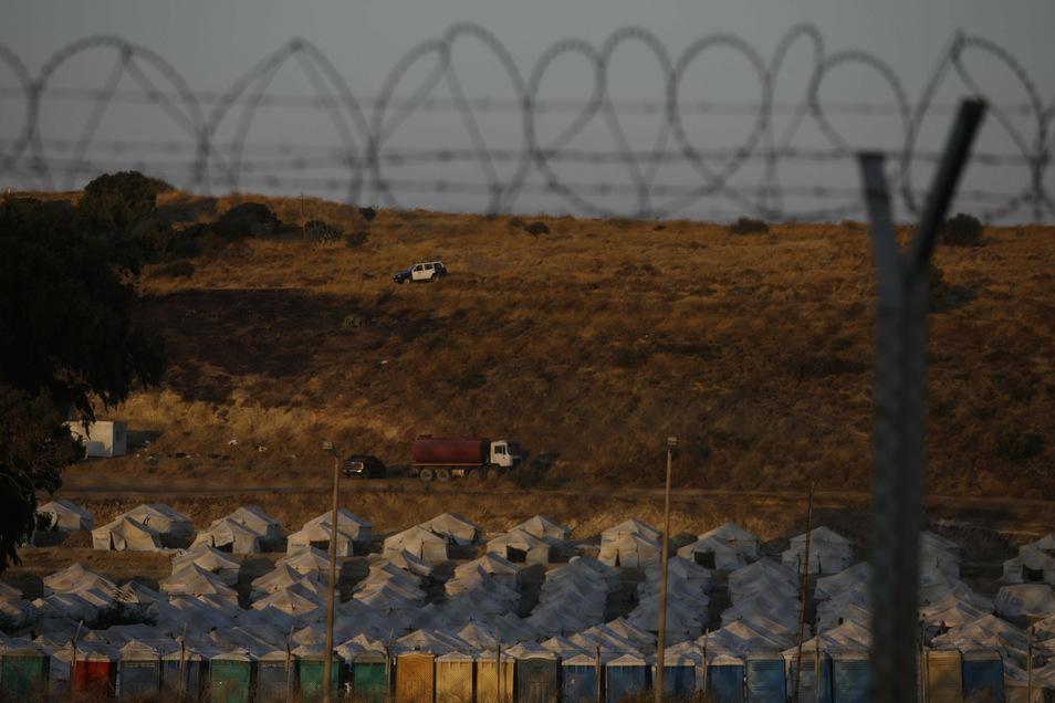 Ein Polizeiauto patrouilliert oberhalb des provisorischen Zeltlagers für geflüchtete Menschen in der Nähe von Mytilini auf Lesbos.