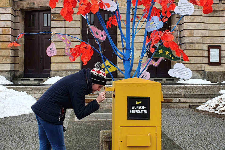 """Prüfender Blick in den Wunschbriefkasten vor dem Staatstheater Cottbus – noch ist Platz für neue Wünsche am farbig-leuchtenden """"Wunschbaum."""