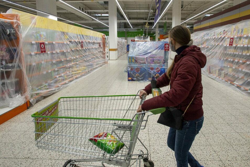 Eine Kundin geht durch einen Prager Supermarkt, in dem Regale mit nicht notwendigen Waren abgedeckt sind. Tschechien befindet sich im Lockdown, die Zahlen steigen dennoch weiter.
