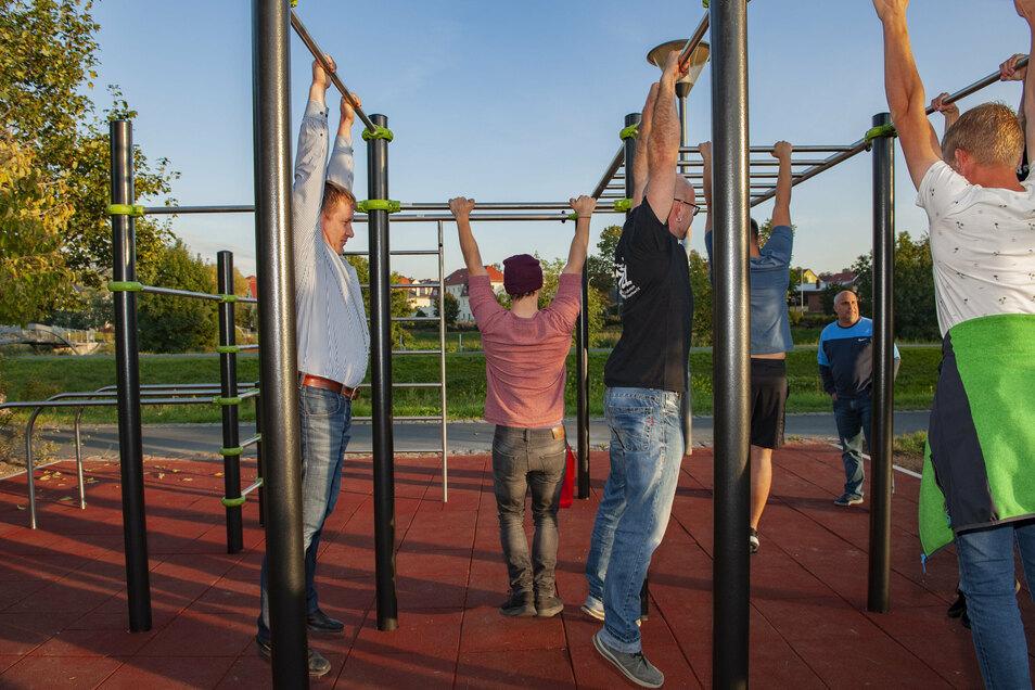 Ja, wer hängt denn da an der Stange? Oberbürgermeister Sven Mißbach (l.) hält sich gut beim kleinen Wettstreit am neuen Streetworkout am KAB. Gemeinsam mit Jugendlichen.