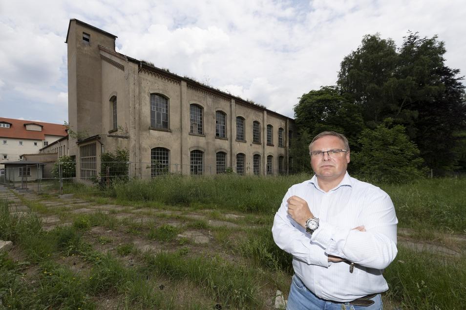 Die Tage der alten Fabrik, vor der Neukirchs Bürgermeister Jens Zeiler steht, sind gezählt. Die Gemeinde will die ehemalige Weberei abreißen lassen, um neue Gewerbeflächen zu erschließen. Das sorgt für Kritik.