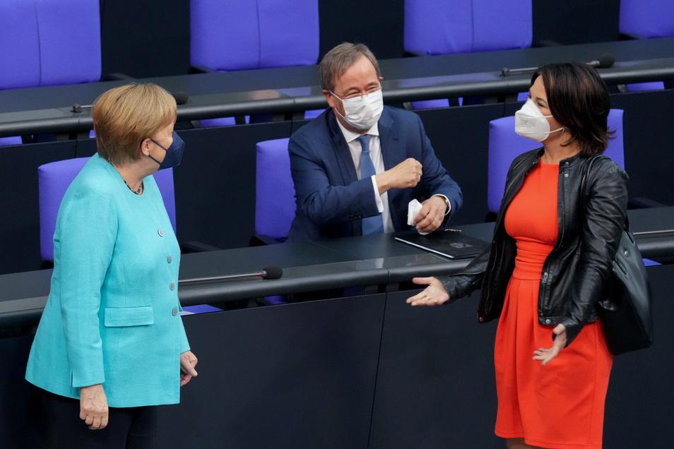 Wer wird ihr nachfolgen? Bundeskanzlerin Angela Merkel (CDU, l) begrüßt Annalena Baerbock (r), Kanzlerkandidatin von Bündnis 90/Die Grünen, und Armin Laschet, CDU-Kanzlerkandidat zu Beginn der Sitzung des Deutschen Bundestags.