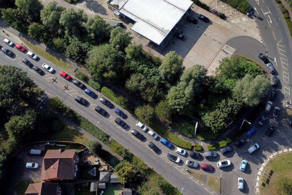 Autofahrer stehen mit ihren Pkw an einer Tankstelle für Benzin in einer langen Warteschlange an. D